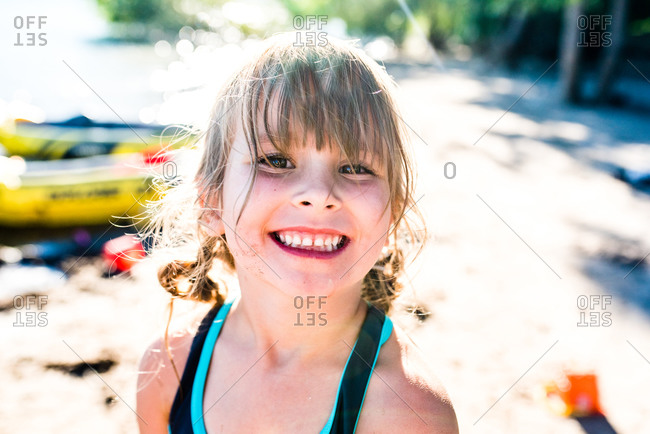 Cute little girl smiling big while playing on beach in summertime