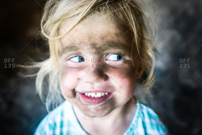 Toddler with dirty face looking off to the side