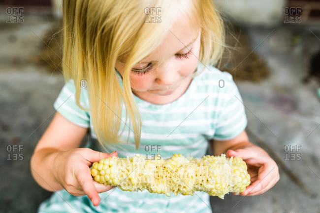 Little blonde girl eating corn on the cob