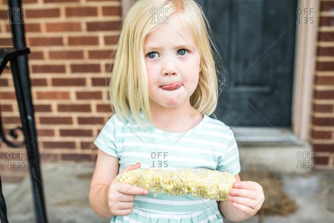 Little blonde girl eating corn on the cob outside