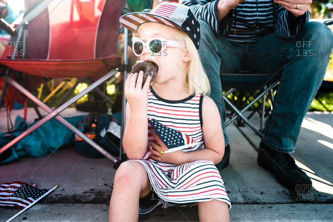 Little girl eating a donut while waiting on a fourth of July parade