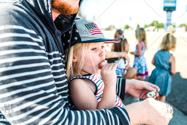 Little girl eating a sucker while sitting with her dad waiting on a fourth of July parade