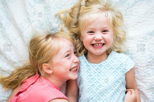Portrait of two little blonde girls lying on white blanket