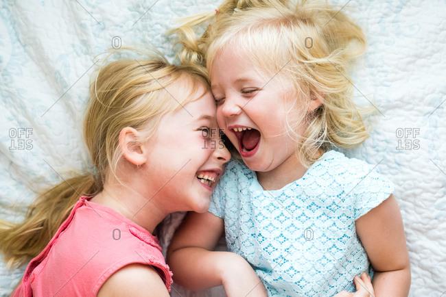 Two little blonde girls lying on white blanket