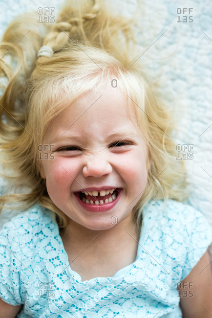 Portrait of a little blonde girl lying on white blanket and laughing
