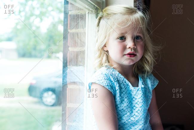 Little blonde girl sitting by window looking worried