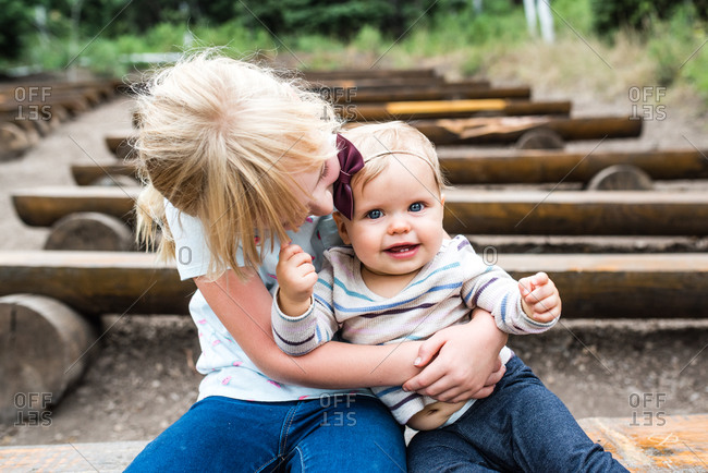 Girl holding her baby sister while sitting on log bench