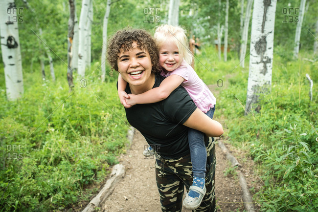 Aunt carrying young girl on her back while walking on trail