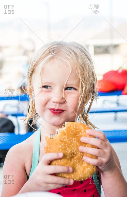 Young blonde girl eating a large hamburger