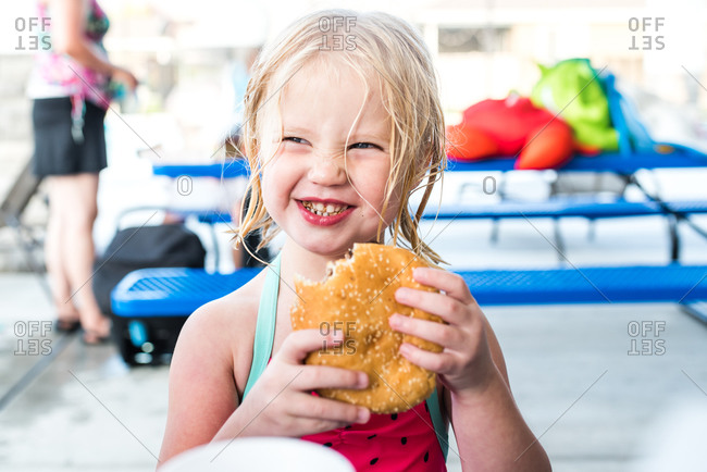 Young blonde girl smiling while eating a large hamburger