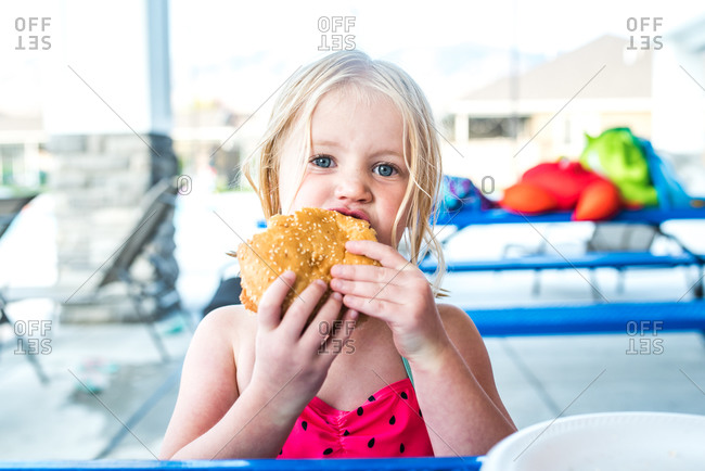 Young blonde girl taking a bite of a large hamburger