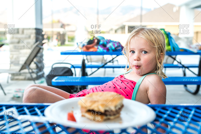 Young blonde girl eating a large hamburger while sitting poolside