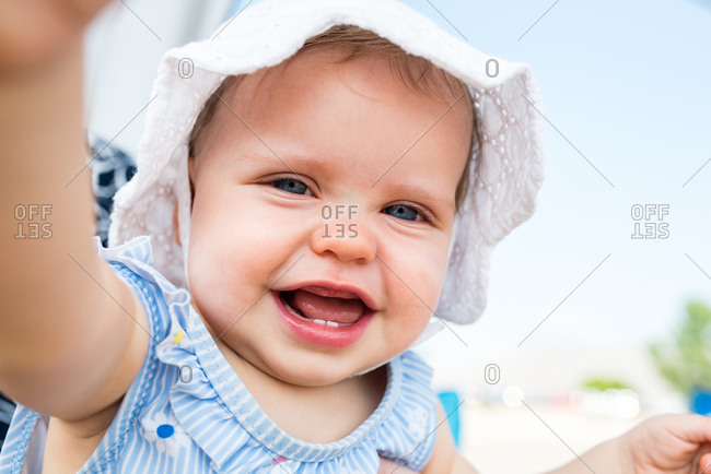 Adorable baby girl with blue eyes wearing a bonnet at the beach