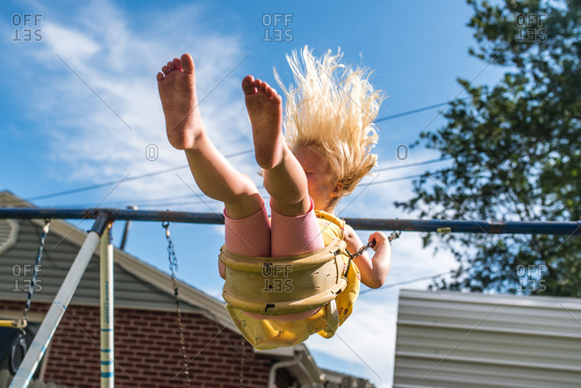 Low angle view of young girl swinging in backyard