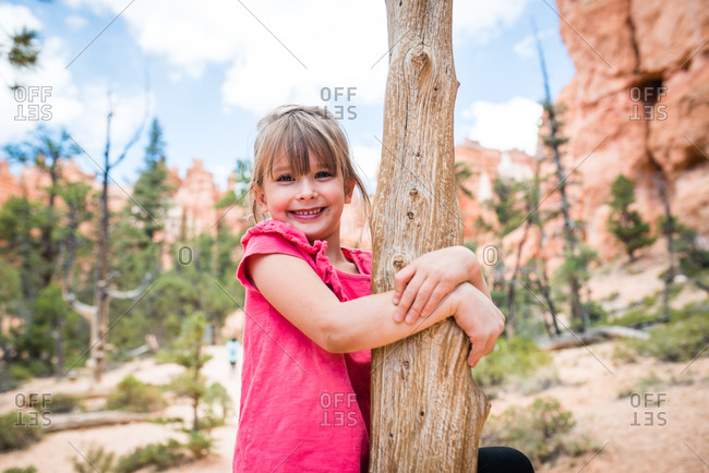 Portrait of a pretty young girl hugging a tree by canyons