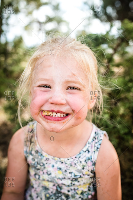 Silly little girl eating with dirt on her face while camping