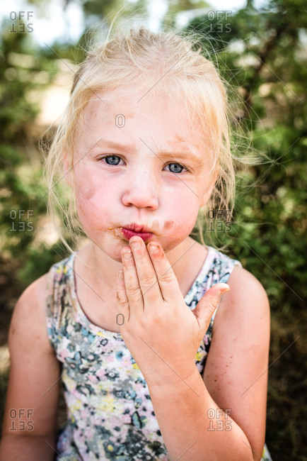 Little girl eating with dirt on her face while camping