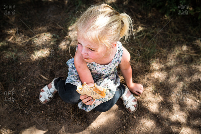 Young girl sitting in the dirt eating a sandwich