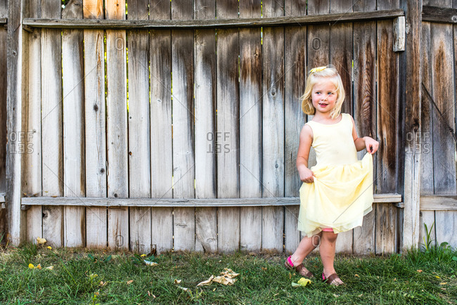 Adorable little girl curtseying in a yellow dress