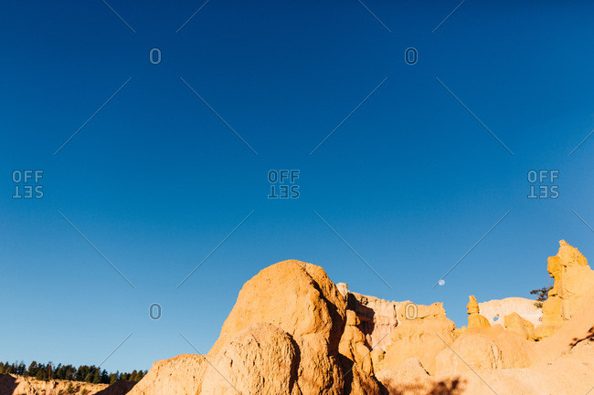 Blue sky and moon rising over Devils Garden in Arches National Park near Moab, Utah