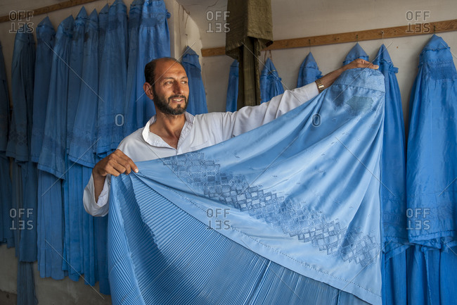 A man holds up a Burqa to show the embroidered patterns