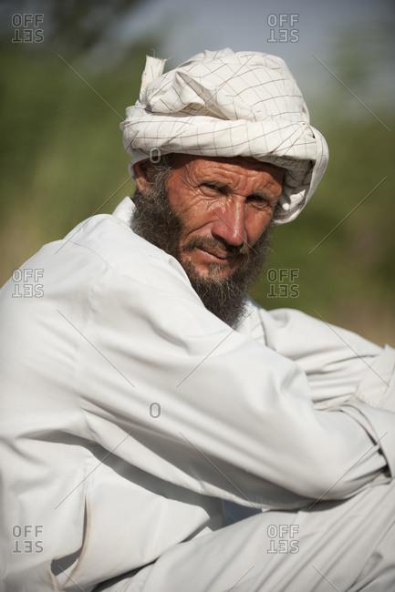 A farmer sits down beside his rice paddies to take a break