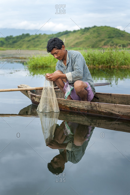 Manipur, India - October 12, 2010: A man fishing from a dugout canoe in Northeast India