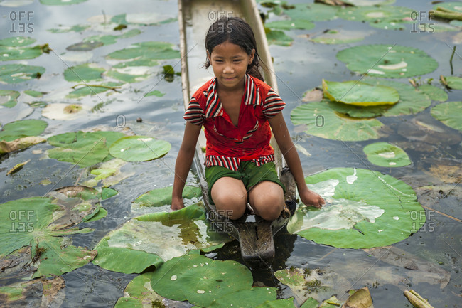 Manipur, India - October 12, 2010: A little girl looks for lotus flowers among the lily pads in India