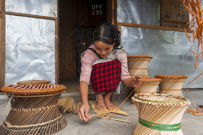 Meghalaya, India - October 22, 2010: A girls makes bamboo stools as an extra source of income in India