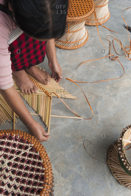 A girls makes bamboo stools as an extra source of income in India