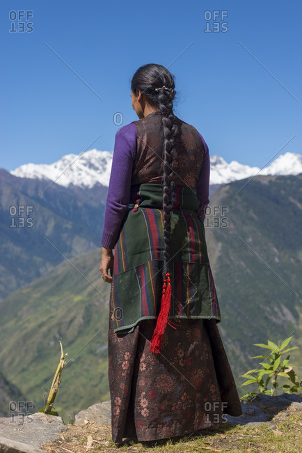 A Tibetan woman with extremely long hair in the Langtang region of Nepal looks out at the Himalayas