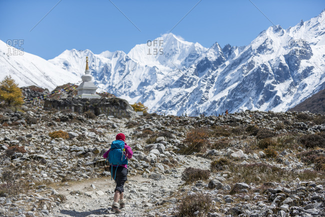 Trekking past a Stupa in the Langtang valley in Nepal with a view of Ganchempo in the distance