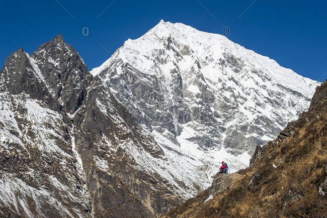 A woman trekking up Kyanjin Ri in the Langtang valley in Nepal with a view of Langtang Lirung in the distance