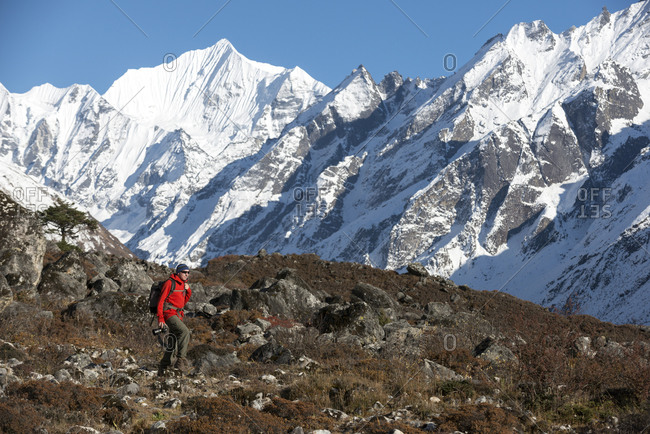 A photographer near Kyanjin Gompa in the Langtang Valley in the Nepal Himalayas with views of Ganchemp peak in the distance