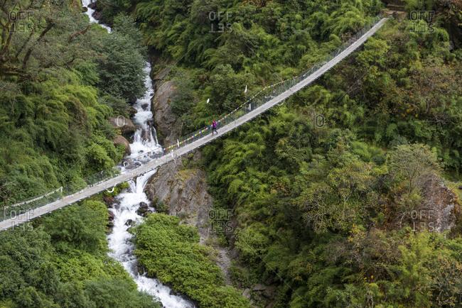 Trekking across a long footbridge above the Langtang Khola near Syabru Besi in the Langtang region of Nepal