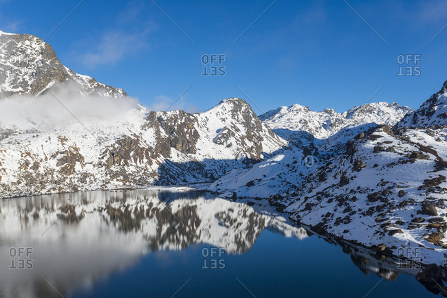 The holy lake at Gosainkund in the Langtang region of Nepal has a glassy like reflection on a still morning in October