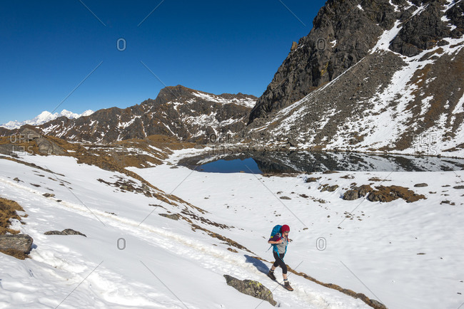 A woman walks past one of the holy lakes of Gosainkund in the Langtang region of Nepal