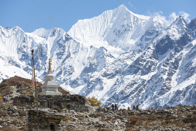 Langtang, Nepal - October 18, 2014: Trekking past a Stupa in the Langtang valley in Nepal with a view of Ganchempo in the distance
