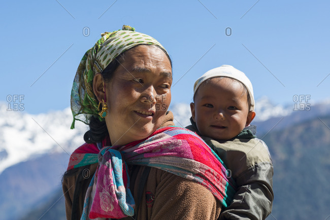 Langtang, Nepal - October 22, 2014: A Nepali woman carrying her baby in the traditional way using a shawl in the Langtang region of Nepal