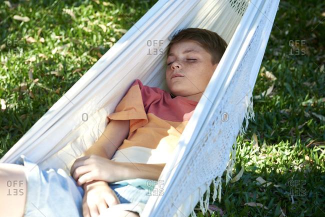 Boy relaxing in hammock alone