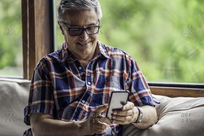 Smiling mature man using smartphone