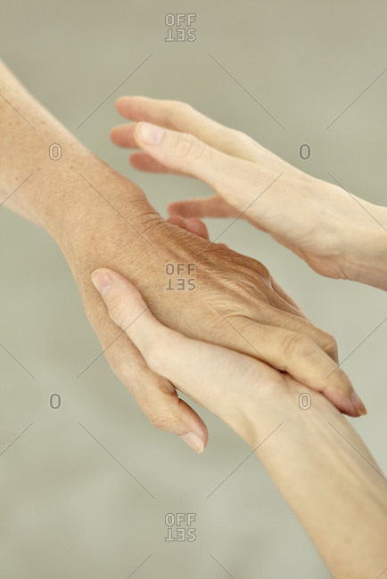 Nurse holding patient's hand softly