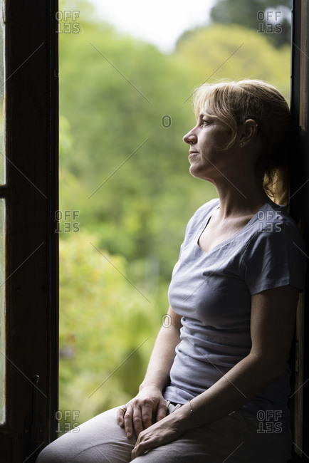 Thoughtful woman sitting on window