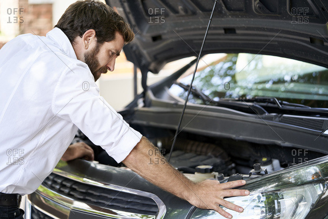 Man standing by car in show room