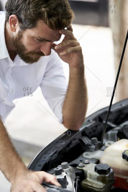 Man looking at car engine