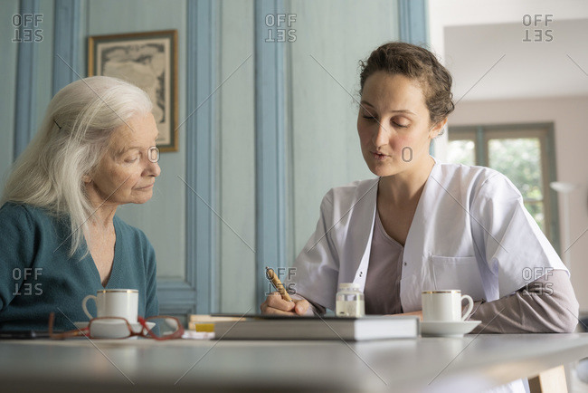 Doctor writing medical history for patient
