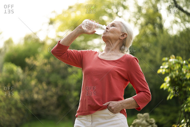 Senior woman drinking water at home