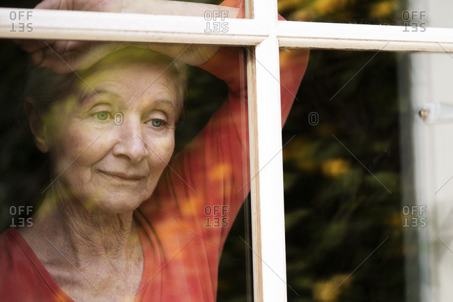 Woman looking through window yearningly, at home