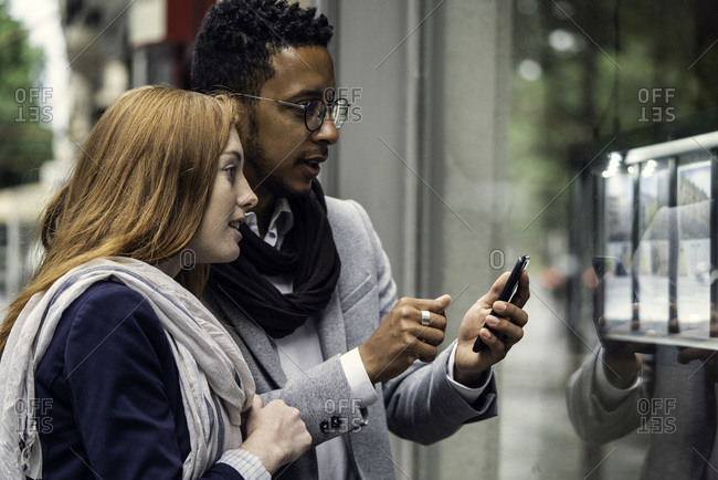 Couple using smartphone at window display