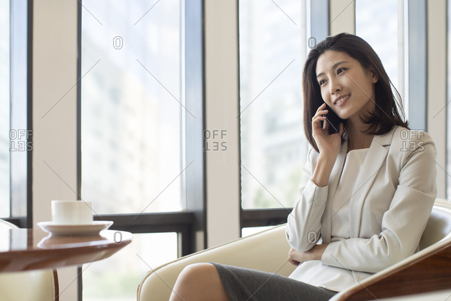 Confident Chinese businesswoman using smartphone in coffee shop